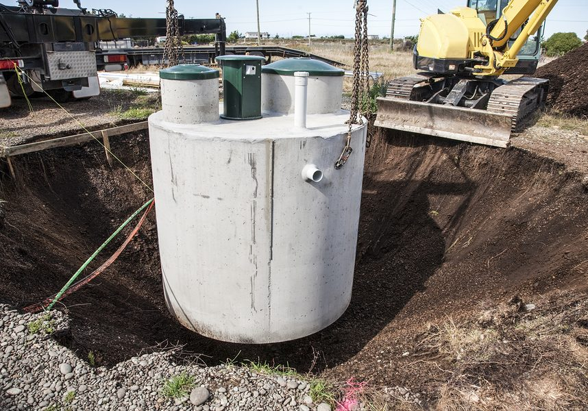 septic tank being lowered into ground.